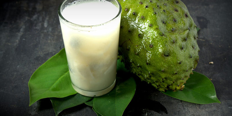 Soursop - Graviola juice in glass with Fresh soursop fruit